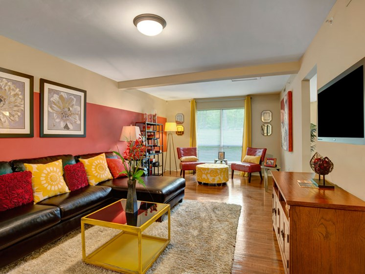 Furnished apartment living room with red walls and wood floors