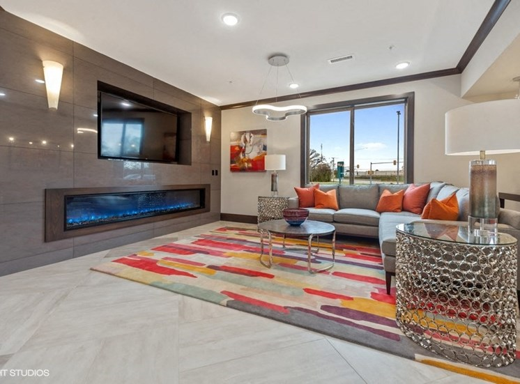 Luxury Community Space Featuring a Flat Screen Television and  Fireplace - Des Plaines Apartments