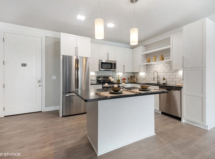Modern kitchen space with stainless steel appliances, granite countertops, and a floating island