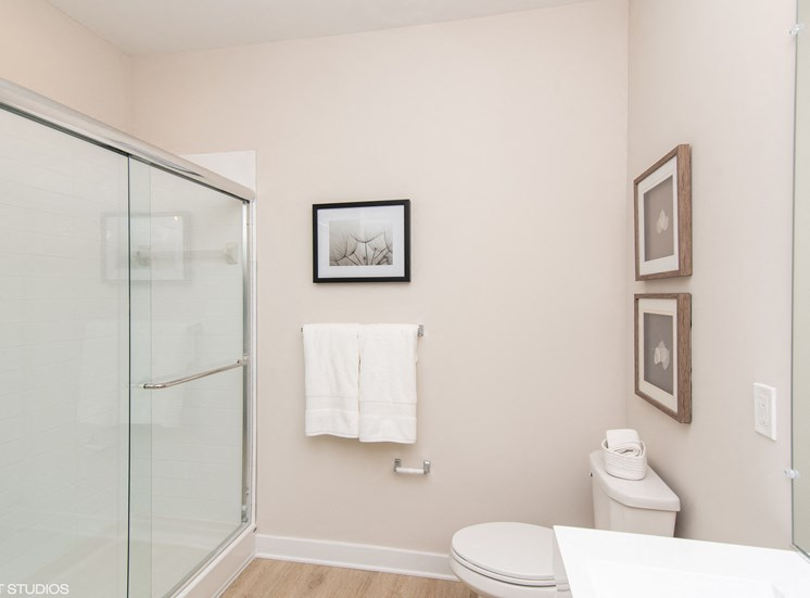 White Bathroom With Shower Enclosure, Toilet, Mirror, and Towels - Apartments in Windsor, CT