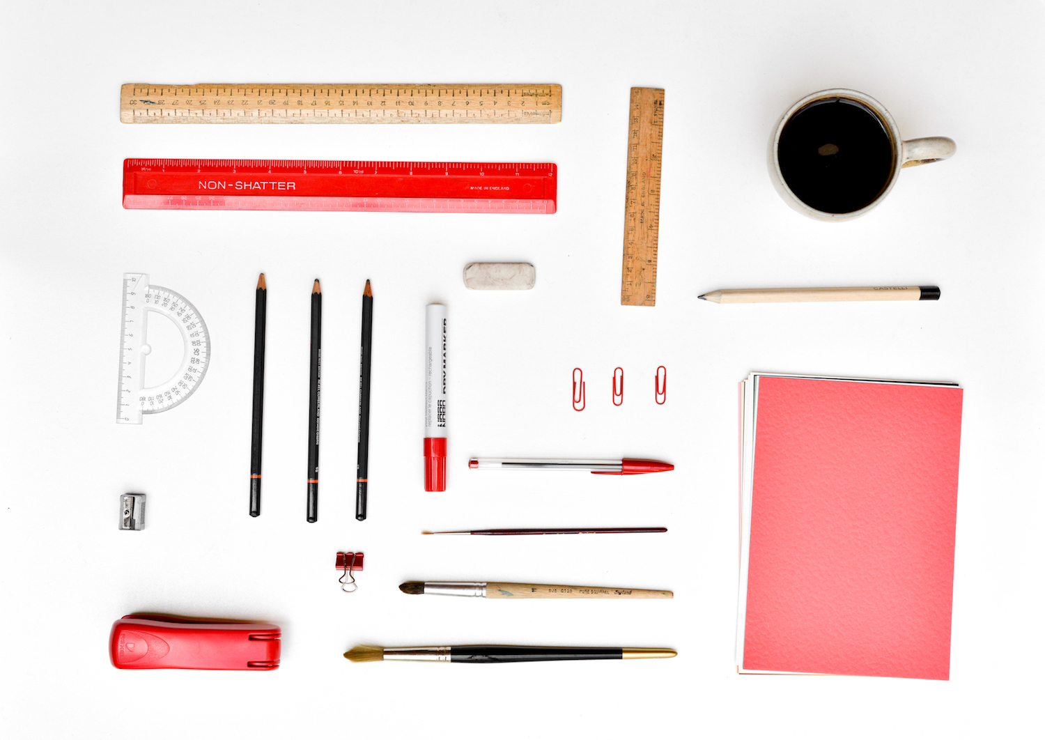 Top view of artistically arranged office supplies on a white desk