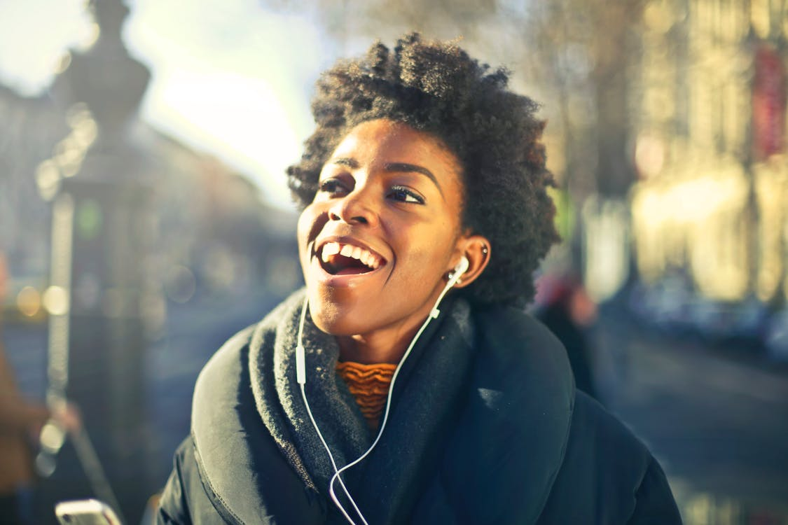 Happy woman listening to music on earbuds outside