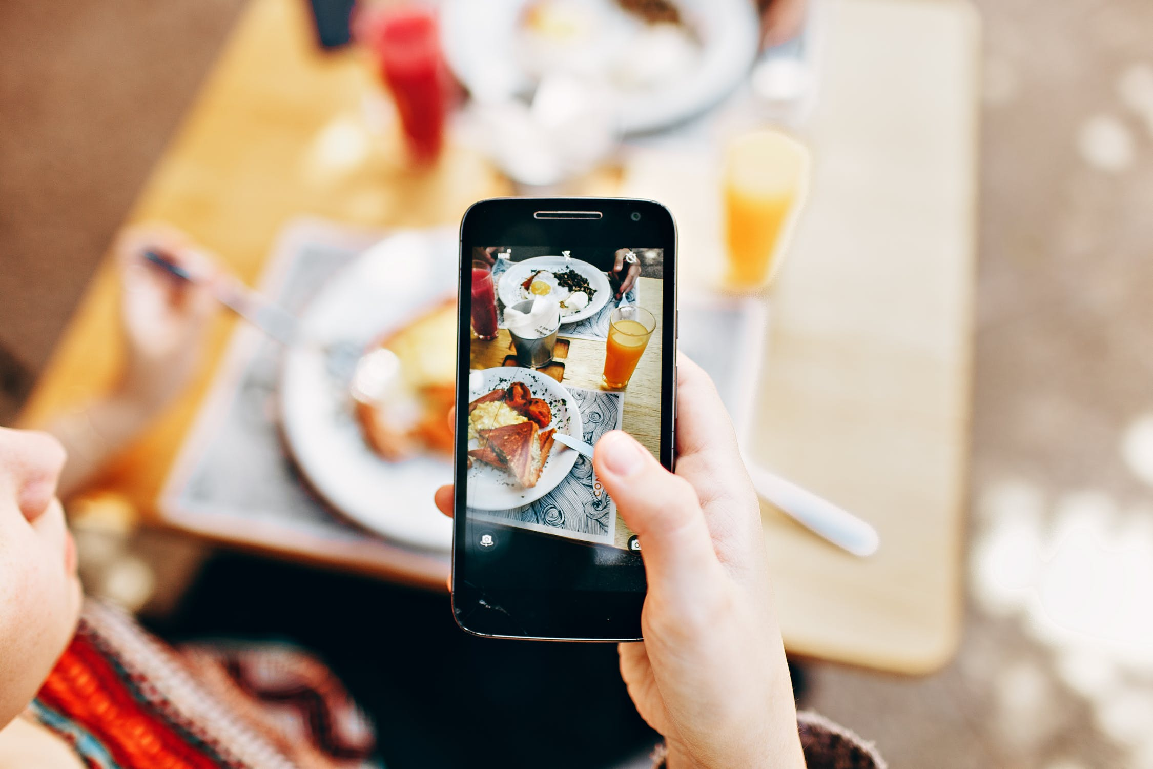 1st person view of someone taking a picture of their food with a smartphone at a restaurant