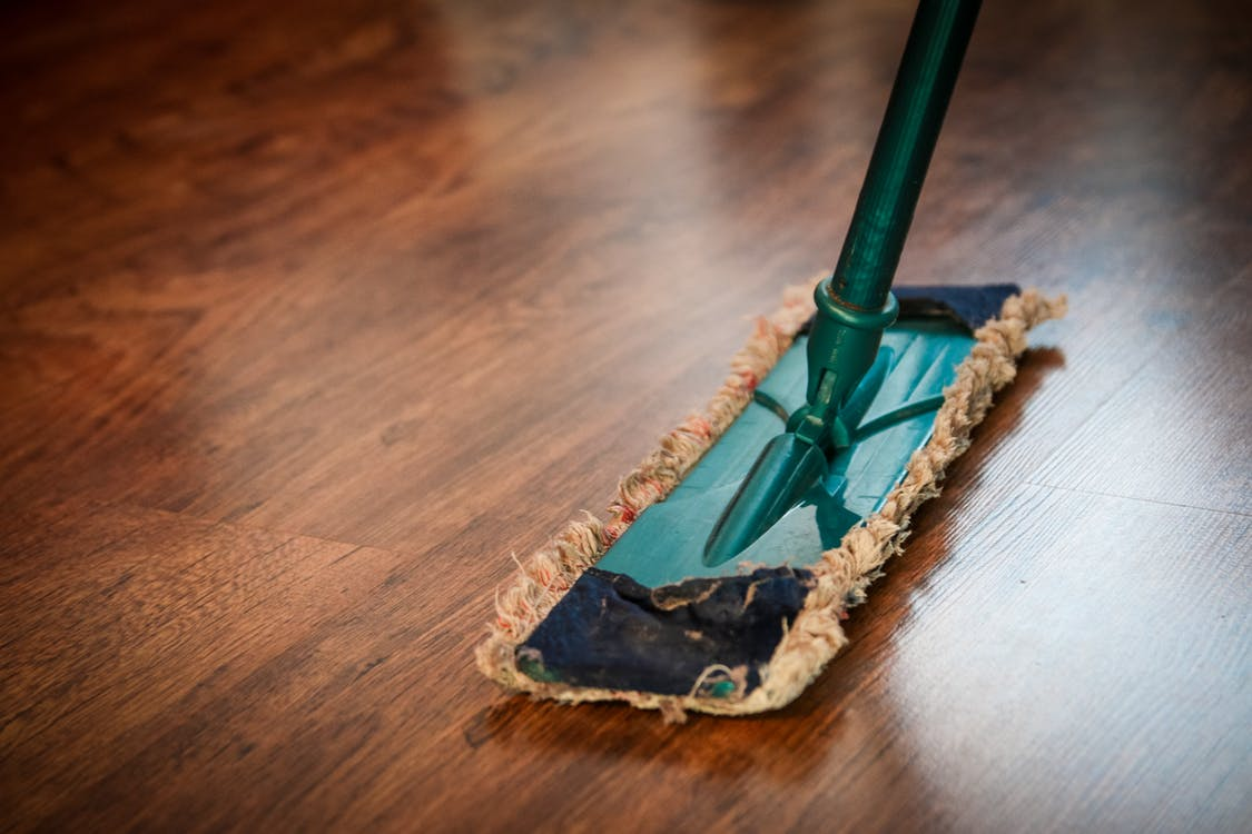 Push broom being pushed across a wood floor