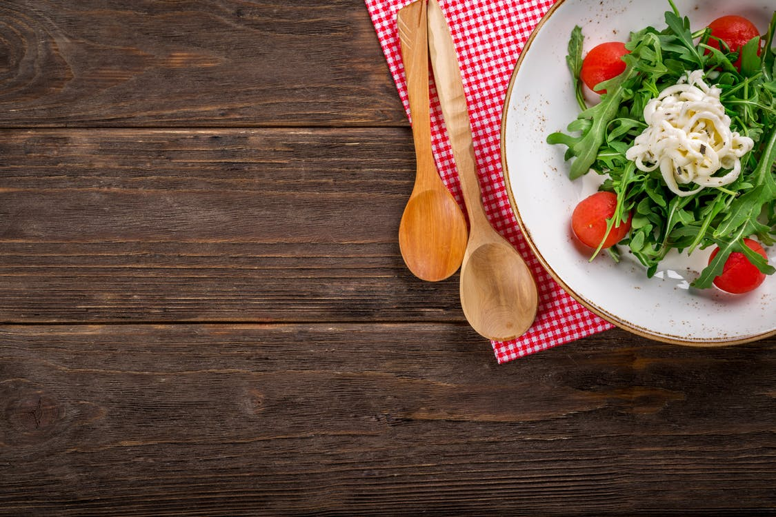 Top view of a salad and wooden spoons on a wooden table