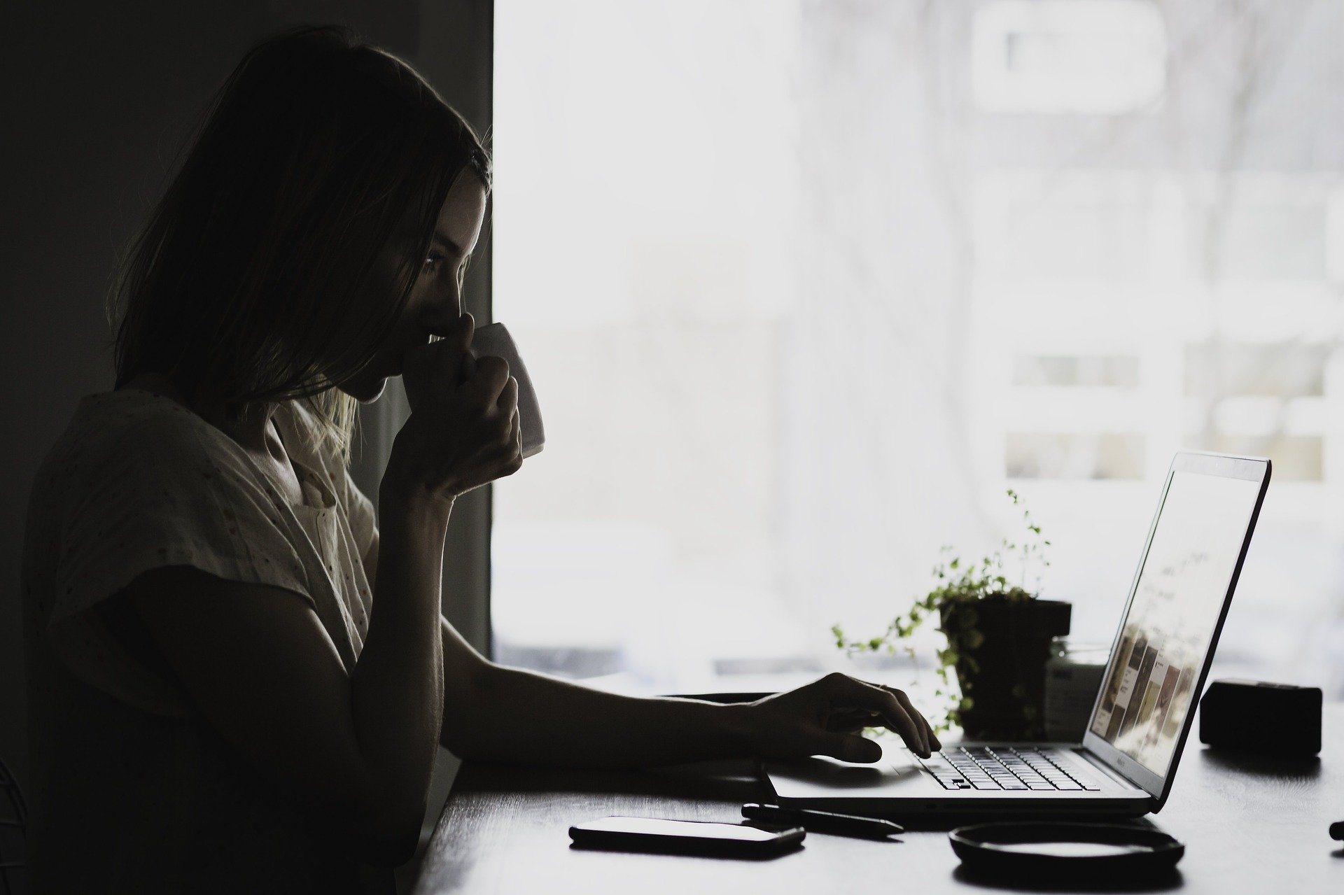 Woman at laptop sipping coffee