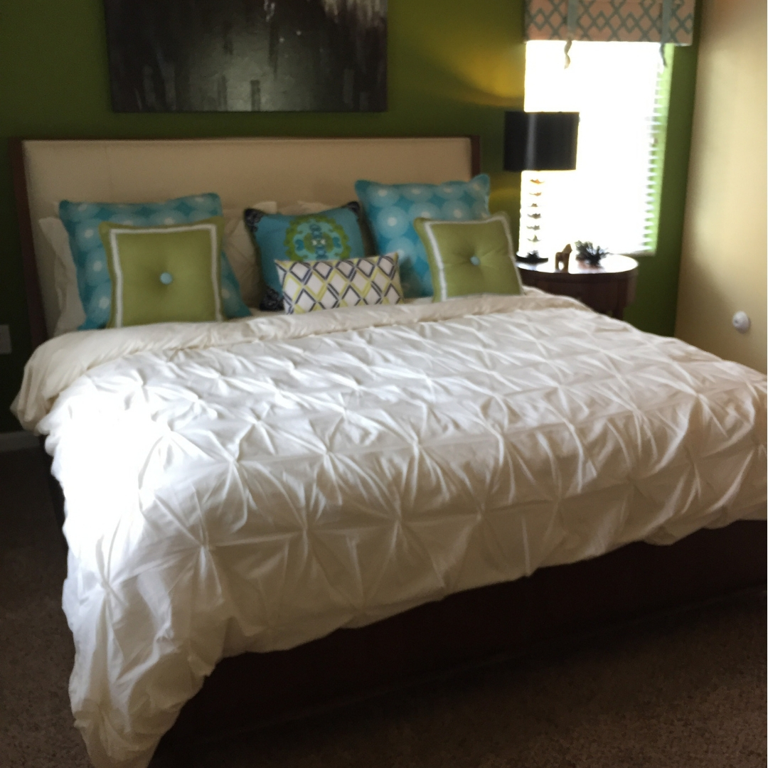 king size bed with white bedspread and decorative pillows