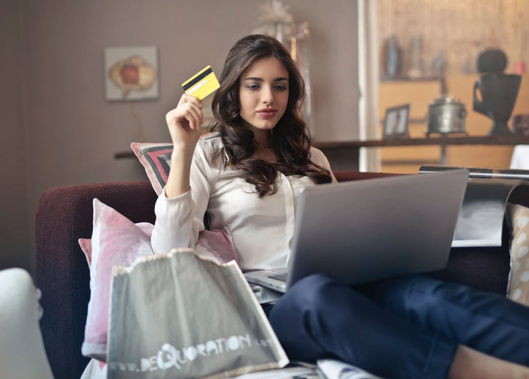 Girl using a laptop at home and holding a credit card