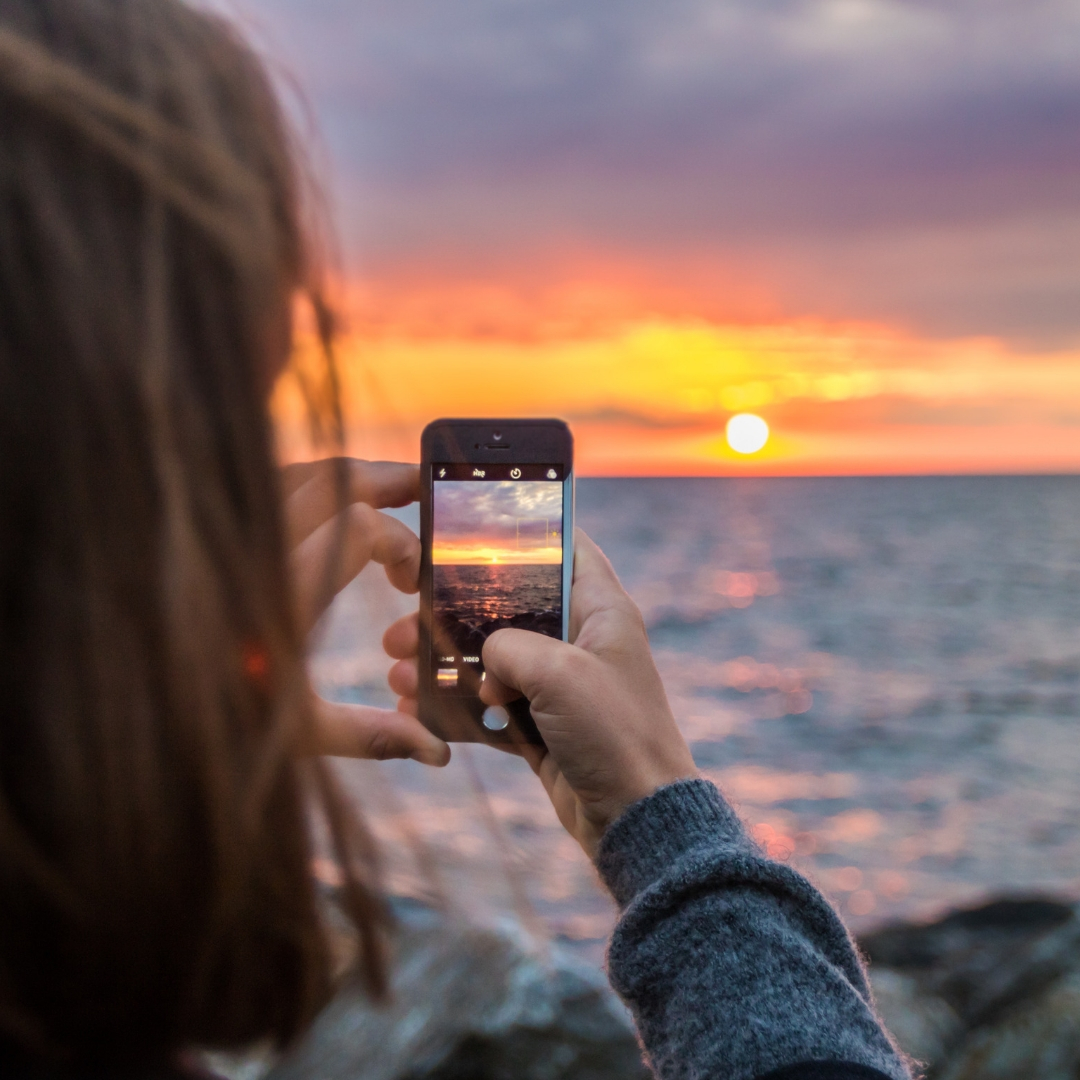 woman taking picture of ocean sunset