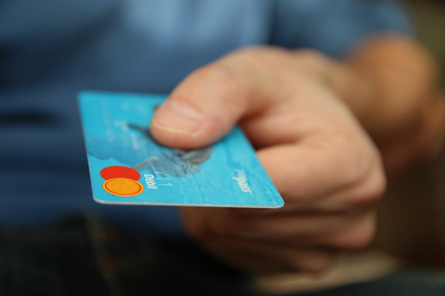 Person's hand, holding a debit card