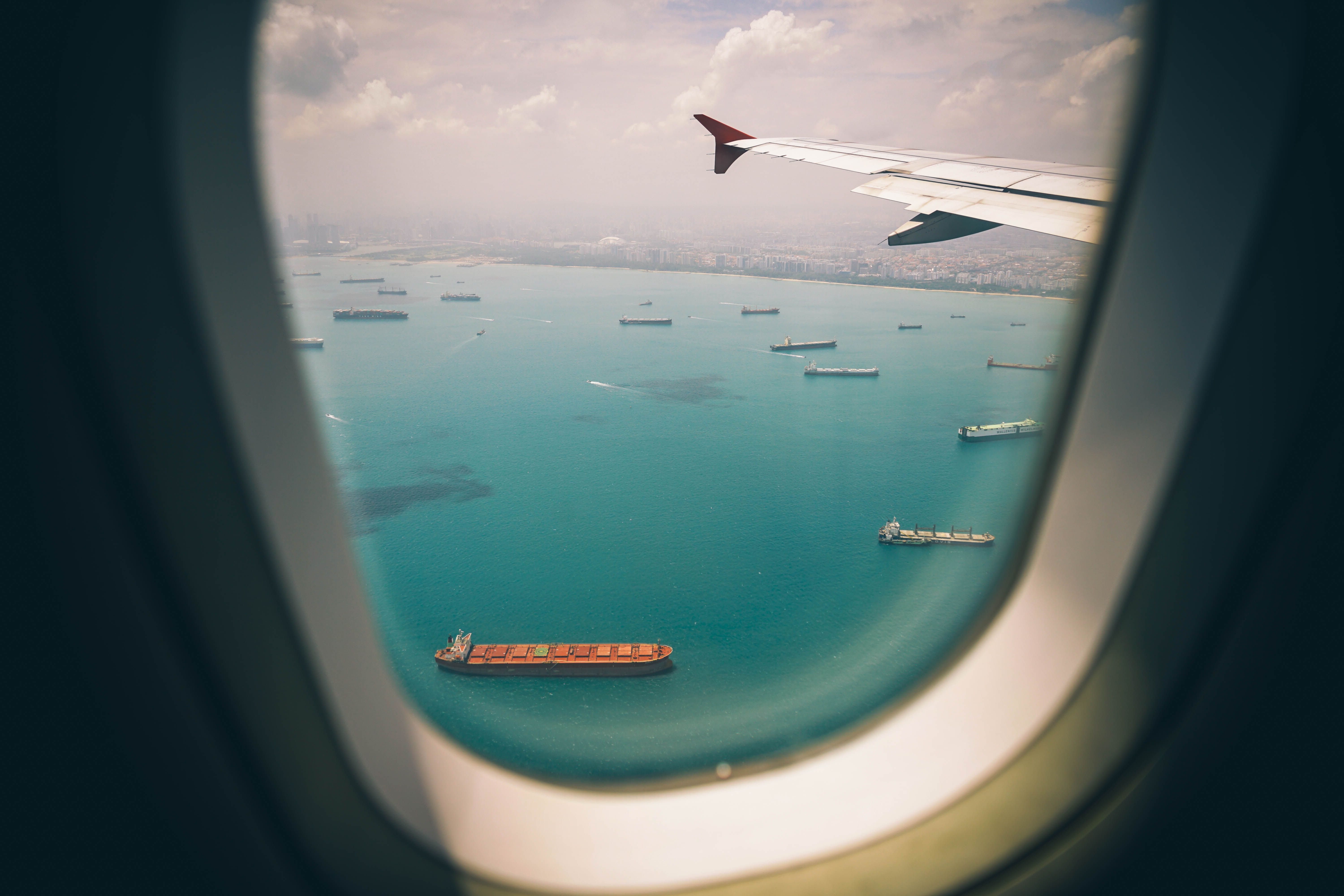 View of a large number of ships on the ocean from the window of an airplane