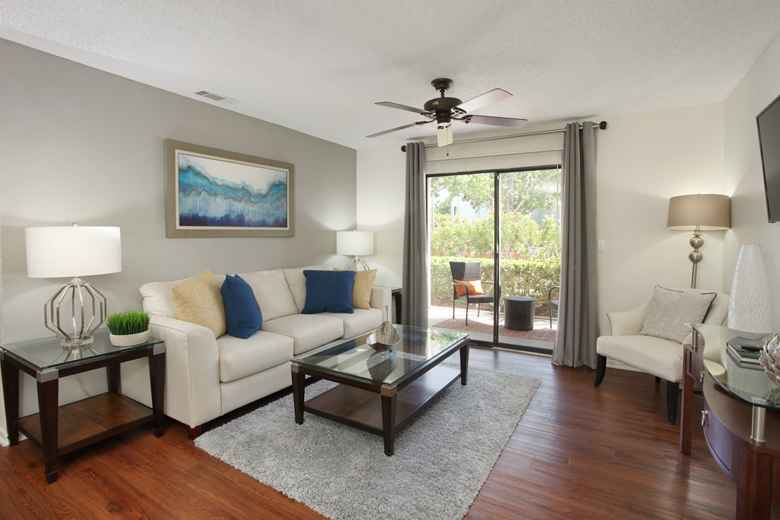 Furnished model living room with wood-look floors and outdoor patio | Coral Club Apartments