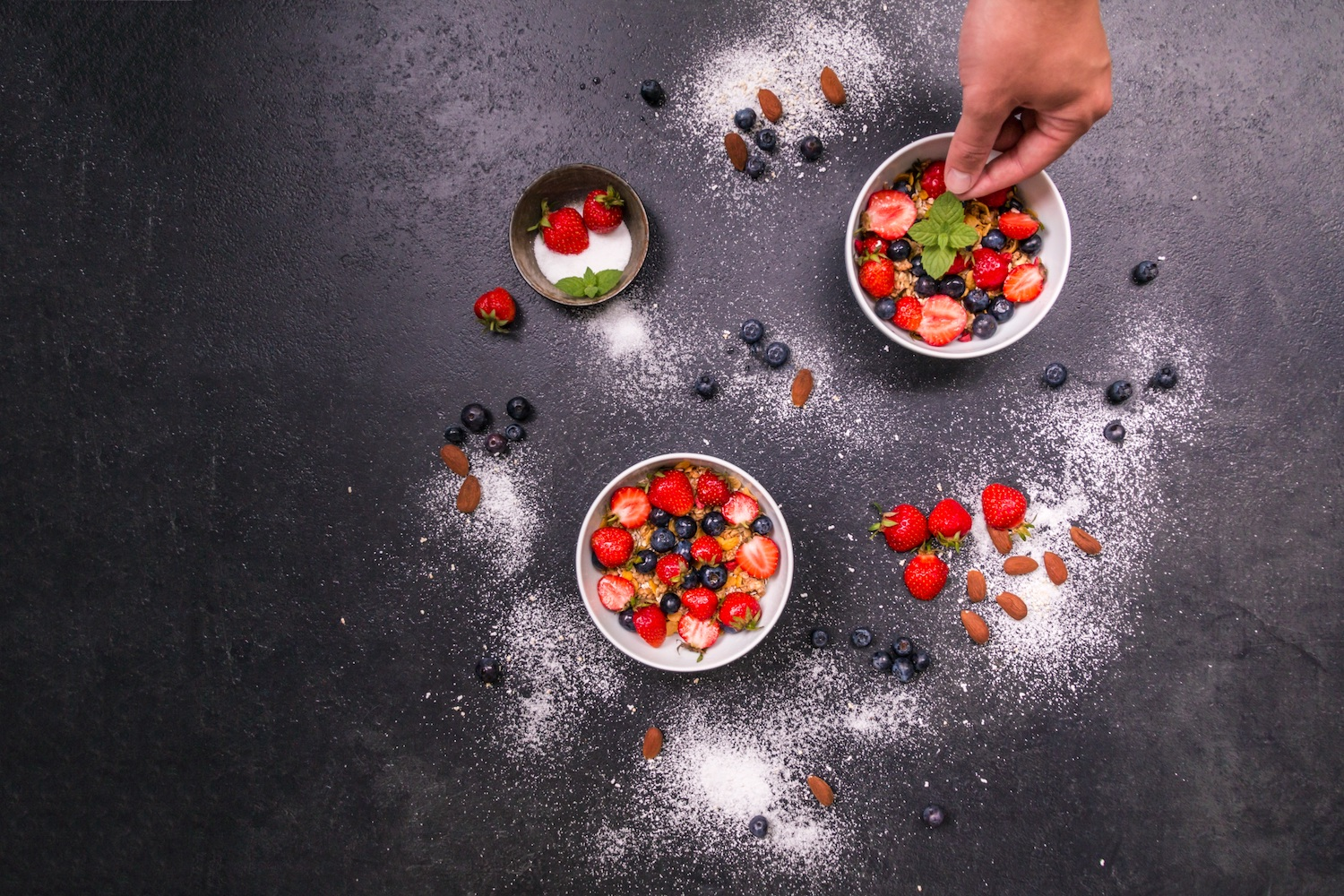 Top view of a person garnishing bowls of mixed fruit